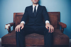 Young businessman on sofa in powerful pose Stock Photo
