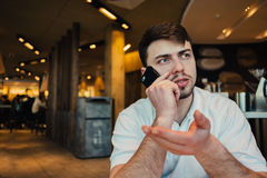 The young businessman solves serious business on the phone sitting in a cozy restaurant. This active gestures. A young businessman with a beard solve serious Royalty Free Stock Image