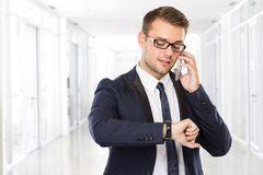 Young businessman speaking on his handphone while looking at his Royalty Free Stock Image
