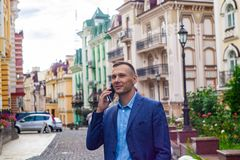 Smiling businessman using phone in city. stock photos