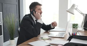 Businessman speaking on mobile phone. Young businessman speaking on mobile phone at office desk stock video footage