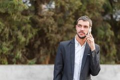 Young businessman speaks by phone on a blurred background of trees stock image