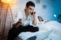 A young businessman speaks on the phone and works behind laptop in bed at home. royalty free stock photo