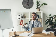 Young businessman spinning soccer ball on finger. At workplace royalty free stock images