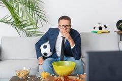 Young businessman sport fan watching match thoughtful stock photo