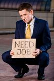 Young businessman squatting with sign Need Job. Financial crisis. Unemployment. Young businessman squatting with sign Need Job outdoors Royalty Free Stock Photos