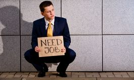 Young businessman squatting with sign Need Job. Financial crisis. Unemployment. Young businessman squatting with sign Need Job outdoors Royalty Free Stock Image