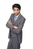 Young businessman standing against white background with arms crossed Stock Image