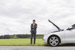 Young businessman standing arms crossed by broken down car at countryside Stock Photos