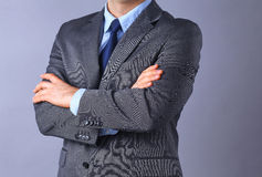 Young businessman standing with arms crossed on gray background Royalty Free Stock Image
