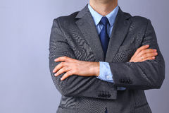 Young businessman standing with arms crossed on gray background Stock Photography