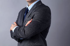 Young businessman standing with arms crossed on gray background Stock Images