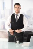 Young businessman standing at desk in office Royalty Free Stock Photography