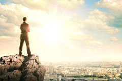 Young businessman standing on edge of rock Stock Images