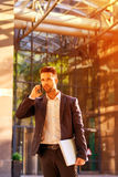 Young businessman standing in front of the office building and t Stock Images