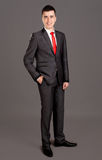 Young businessman standing on grey background Royalty Free Stock Photos