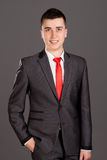 Young businessman standing on grey background Stock Photography