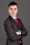 Young businessman standing on grey background Stock Photos