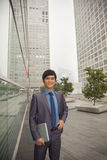 Young businessman standing with his laptop out side of CBD, portrait Stock Photo
