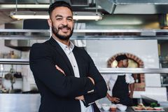 Young businessman standing in his restaurant. Portrait of young businessman standing in his restaurant with staff in kitchen. Proud restaurant owner standing royalty free stock photo