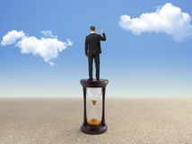 Young businessman standing on hourglass Royalty Free Stock Images