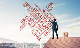 Young businessman standing on house roof and writing leadership Royalty Free Stock Photos