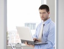 Young businessman standing with laptop in hand Royalty Free Stock Photos