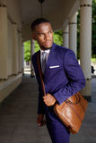 Young businessman standing with leather shoulder bag Stock Photo