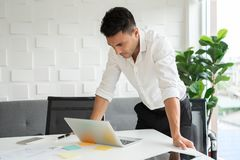 Young businessman is standing and looking at laptop. royalty free stock images