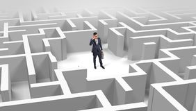 Businessman standing in a middle of a maze royalty free stock photo