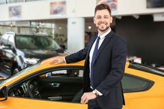 Young businessman standing near auto in salon. Buying new car royalty free stock photography