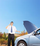 Young businessman standing near a broken car and talking on a mo Stock Images