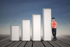 Young businessman standing next to growing bar chart Stock Photography