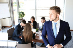 Young businessman. Standing in office with his collegue on the background Stock Photography