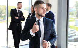 Young businessman. Standing in office with his collegue on the background Royalty Free Stock Images