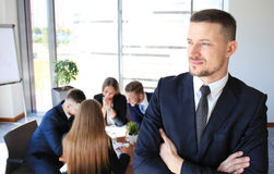 Young businessman. Standing in office with his collegue on the background Royalty Free Stock Photography