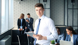 Young businessman. Standing in office with his collegue on the background Stock Images