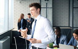 Young businessman. Standing in office with his collegue on the background Stock Photo