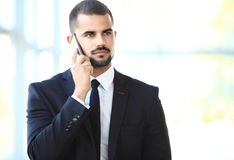 Young businessman standing in office lobby, using smartphone Royalty Free Stock Images