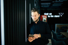 Young businessman standing in office lobby, using smartphone. Royalty Free Stock Photo
