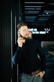 Young businessman standing in office lobby, using smartphone. Royalty Free Stock Image
