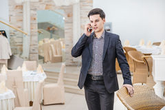 Young businessman standing in office and talking on the phone. Y Stock Photos