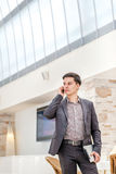 Young businessman standing in office and talking on the phone. Y Royalty Free Stock Photos