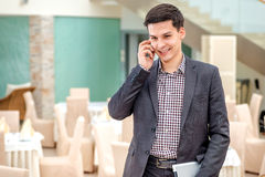 Young businessman standing in office and talking on the phone. Y Stock Images