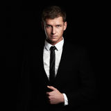 Young Businessman Standing On Black Background. Handsome Man In Suit And Tie