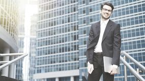 A young businessman standing in the open-air smiling, laughing royalty free stock images