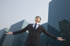 Young businessman standing outside with arms outstretched Royalty Free Stock Photos