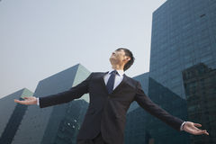 Young businessman standing outside with arms outstretched Stock Image