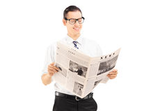 Young businessman standing and reading a newspaper Royalty Free Stock Image