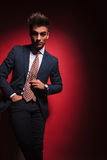 Young businessman standing in red studio with hand in pocket Stock Photo